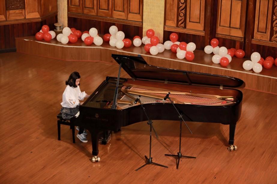 Các ngón tay nhảy múa trên phím đàn piano, trong không gian ấm cúng của phòng hòa nhạc